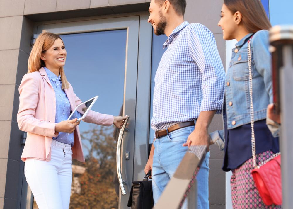 eine attraktive Immobilienmaklerin begrüsst Kaufinteressenten vor der Haustür