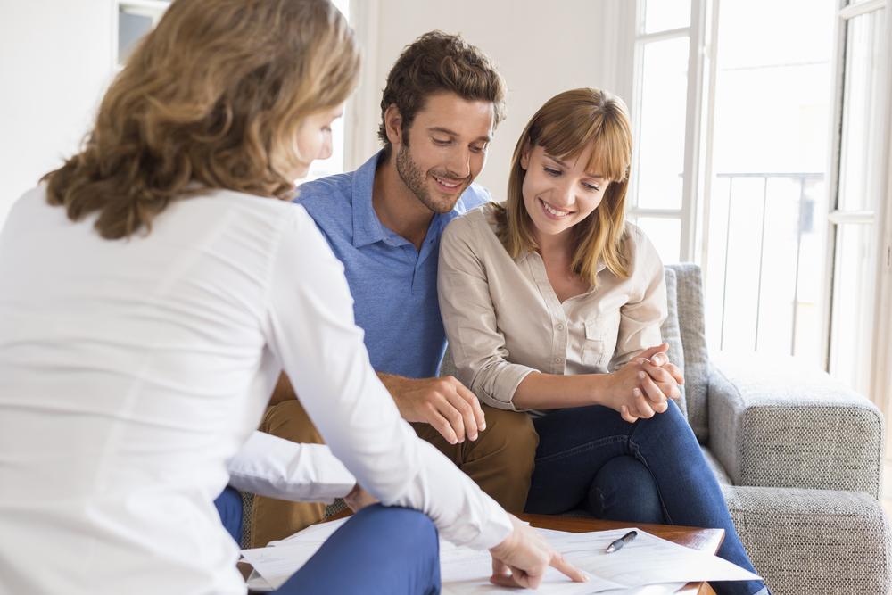 Immobilienmaklerin bespricht mit Kaufinteressenten Vertragsunterlagen. Im Hintergrund ist ein Wohnzimmer zu sehen