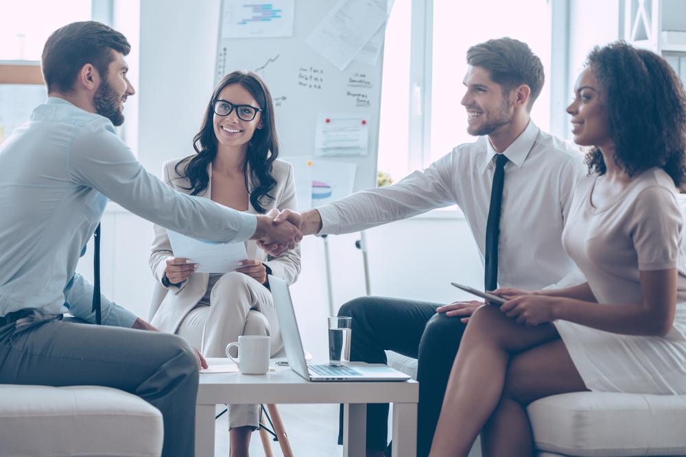 Vier Personen führen ein Bewerbungsgespräch. Im Hintergrund ist das Büro zu sehen.