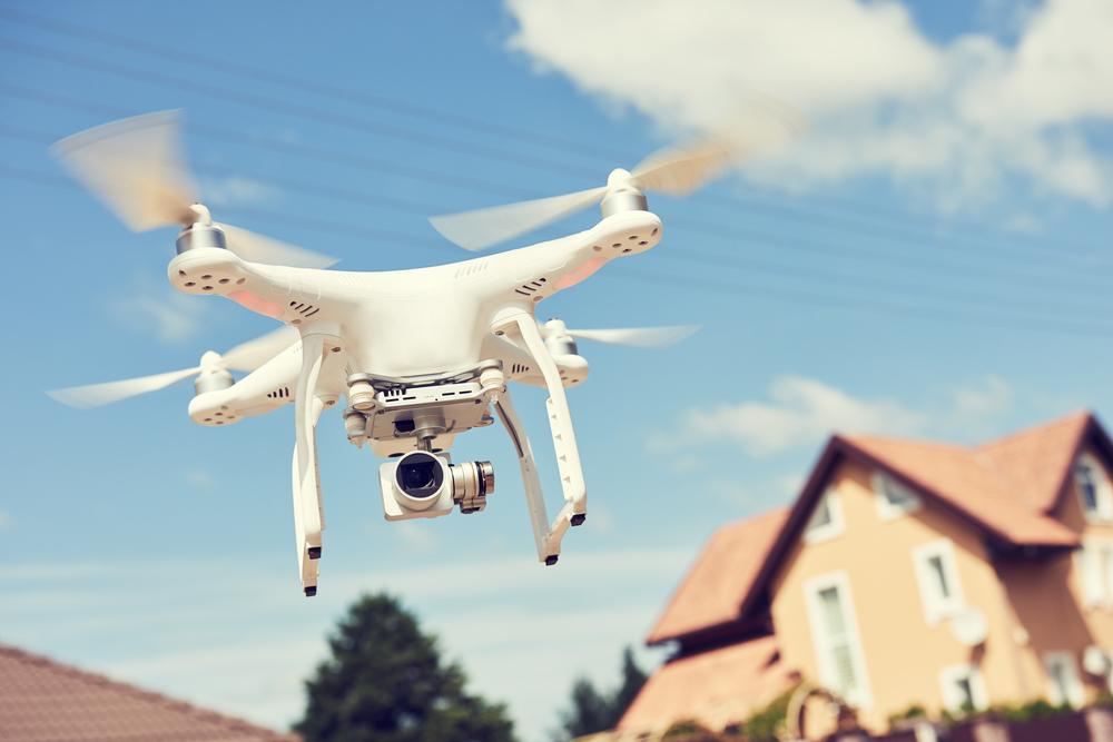 eine Drohne fliegt um ein Haus und macht aufnahmen